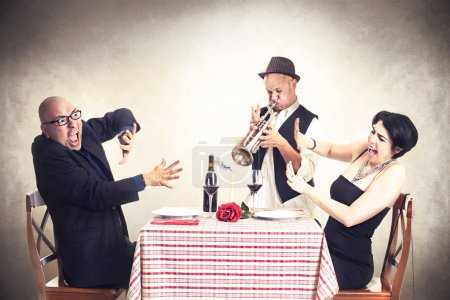 Photo for Angry couple disturbed by a trumpet musician while having dinner - Royalty Free Image
