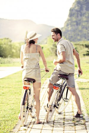 Photo for Couple in love have a ride with bicycles in the nature - Royalty Free Image