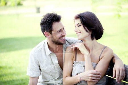 Couple in love seated together on a bench
