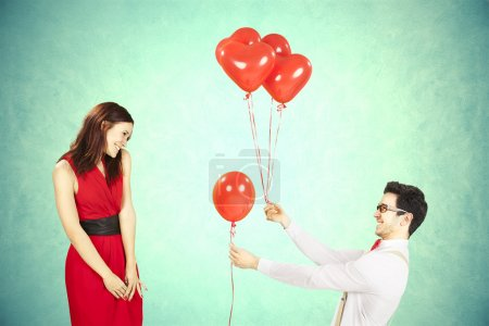 Photo for Man approaching woman giving her red heart shape balloons with light blue background - Royalty Free Image