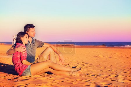 Photo for Sweet Young Couple Sitting on Sand at the Beach During Afternoon While Looking Afar. - Royalty Free Image