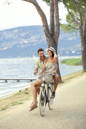Photo for Man carrying his woman on a bike in the lake zone - Royalty Free Image