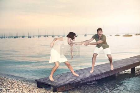 Photo for Man try to push her woman int water - Royalty Free Image