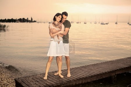 Couple flirting on the boardwalk at the lake