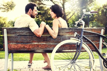 Couple in love sitting together on a bench with bikes