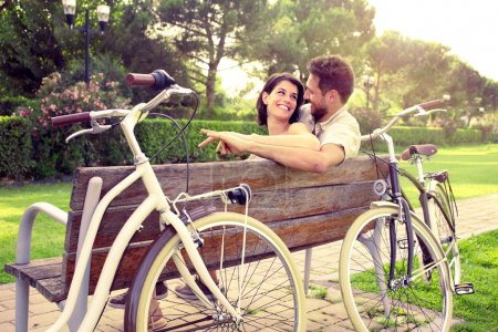 Couple in love sitted togheter on a bench with bikes beside