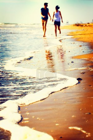 Happy couple playing on the seashore at sunset