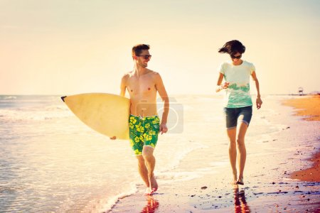 Photo for Surfers couple running on the seashore at sunset - Royalty Free Image