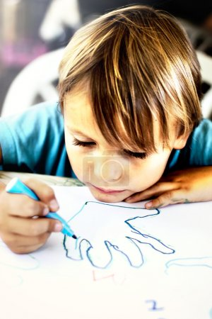 A young boy is doing drawing