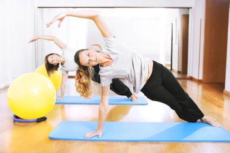 Photo pour Deux femmes faisant un exercisen de remise en forme en synchronie - image libre de droit