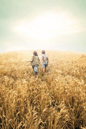 Photo pour Enfants qui courent au blé pour le coucher du soleil - image libre de droit