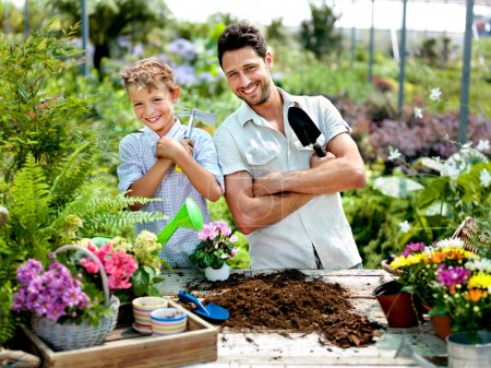 Father and son playing with work tools in a greenhouse