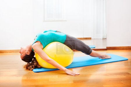 Photo pour Enseignant en faisant des exercices du corps sur une boule jaune - image libre de droit