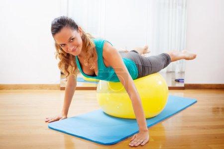 Photo pour Femme faisant les exercices du corps sur une boule jaune - image libre de droit