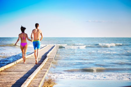 Sporty couple running on the dock at the sea