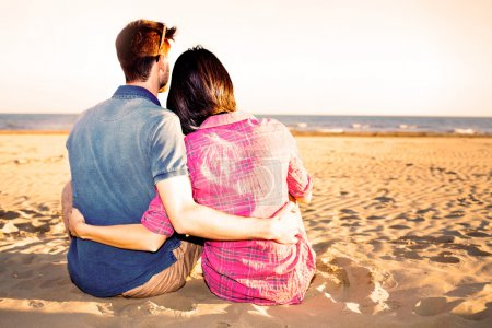Photo for Sweet Couple Sitting on Sand at the Beach at sunset - Royalty Free Image