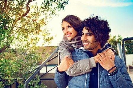 Photo pour Portrait de couple souriant avec les bras l'un autour de l'autre à l'extérieur et regardant vers le côté - image libre de droit