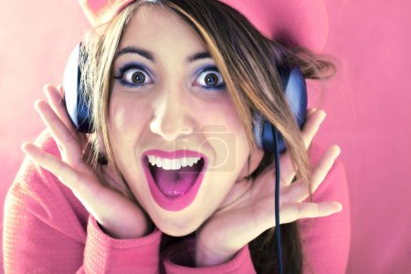 Happy shocked woman in pink listening to good sound
