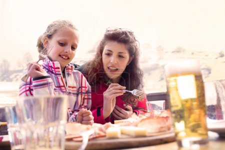 Mom and daughter have lunch in a chalet in the mountain