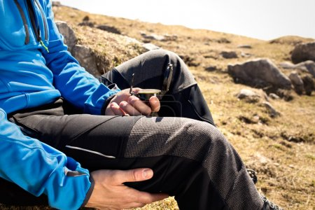 Man seeks direction with the compass in the mountains