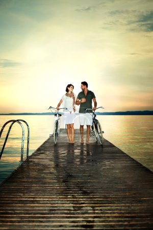 couple in love pushing bike on a boardwalk at the lake