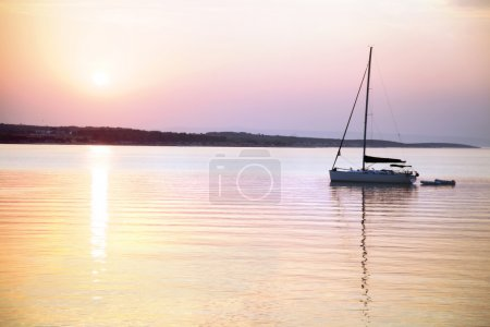 sailing boat floats in the calm sea at sunrise