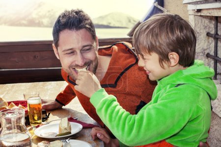 father and son having lunch in a chalet in the mountain