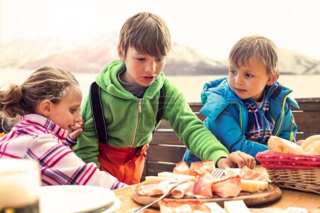 sons have lunch in chalet in the mountain