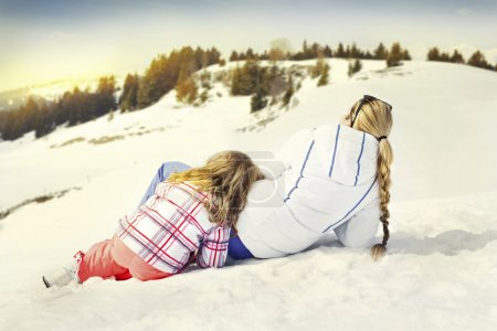 Mother hugs his daughter affectionately in the snow