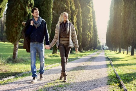 Photo for Couple walking in the leafy avenue - Royalty Free Image