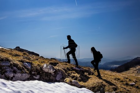 Silhouettes of hikers walking in the mountains breathing clean air