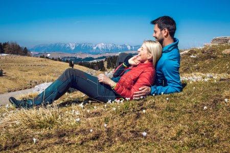 Photo pour Deux randonneurs avec sac à dos reposant sur le sommet de la montagne - image libre de droit