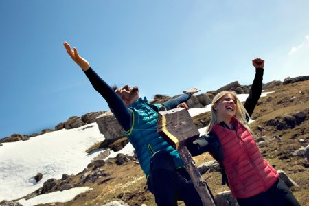 couple hikers exulting for the reaching the goal in the mountain