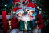Dvě děti, otevírání vánoční dárek s paprsky světla