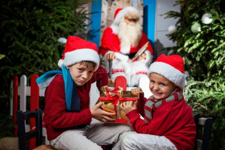 two small Santa Clauses contending a gift