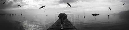Photo for Elegant woman repairing from the rain of blacks umbrellas in a surreal landscape sea - Royalty Free Image
