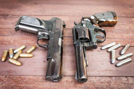 Black revolver gun and Semi-automatic 9mm gun on wooden backgrou