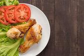 Grilovaná kuřecí stehýnka a zelenina na dřevěné pozadí