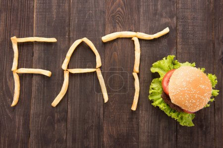 French fries with burger forming word fat on wooden background