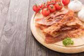 Opečená slanina, rajčata a česnek na dřevěné desce