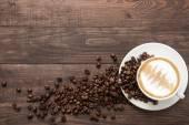 """Постер, картина, фотообои """"Чашка кофе и кофейных зерен на деревянных фоне. Вид сверху"""""""
