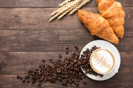 Photo for Coffee cup and fresh baked croissants on wooden background. Top View. - Royalty Free Image