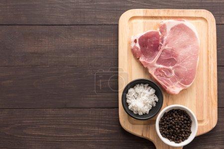 Top view raw pork chop steak and salt, pepper on wooden backgrou