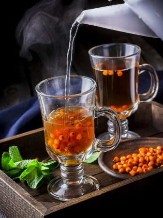 Hot tea flowing in glass cup with berries.