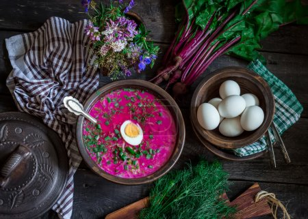 Russian cold soup with beetroot, bowl,spoons,greenery on dark wooden table. Style rustic.