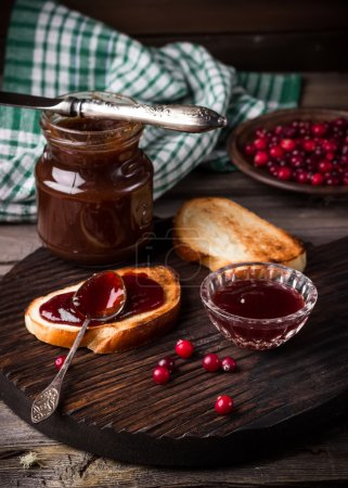 Toasts, jam and cowberry on dark cutting board.