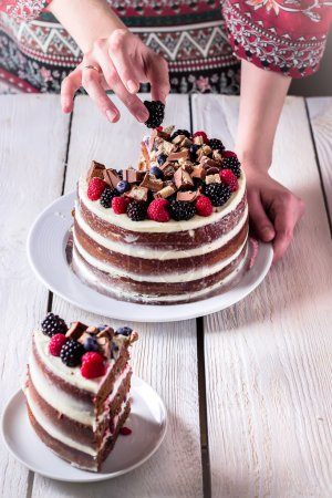 Photo pour Layer cake on white wooden table and one slice on saucer. Selective focus. - image libre de droit