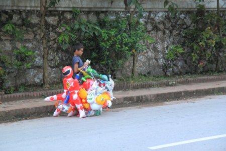 Photo pour Luang Prabang Laos - 15 mai: Unenfant non identifié compte l'argent de la vente - 15 mai 2012 à Luang Prabang Laos. L'Enquête sur le travail des enfants indique qu'environ 15 pour cent des enfants laosans sont employés dans l'activité économique. - image libre de droit