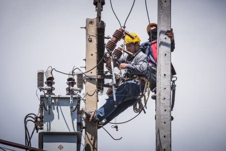 Electricians working together on the electricity pole