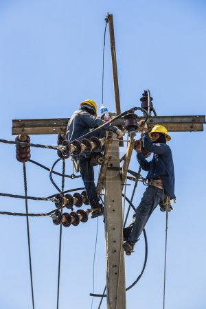 Electricians resting while working on the electricity pole